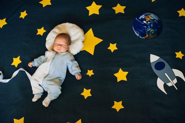 男の子はロケットと惑星で星空の背景で眠る