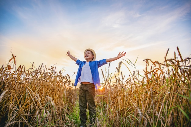 Baby boy standing in a field of wheat ears wide open hands looking into the distance smiling with happiness.