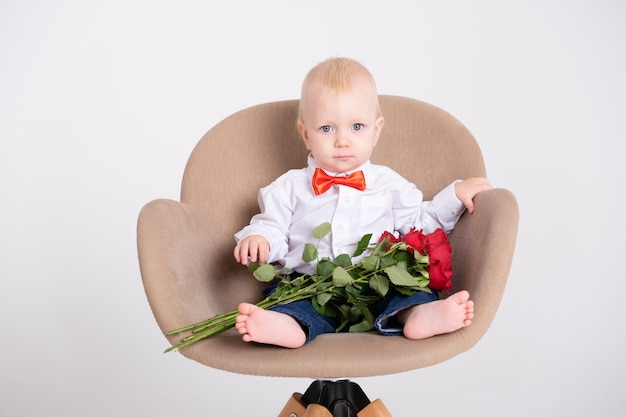 Baby boy in suit and red bow tie holds bouquet of roses sits in chair on a white background.