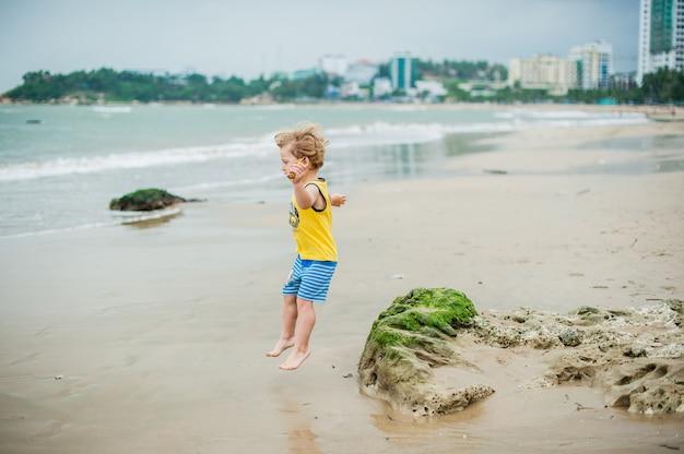 Baby boy walking on the sandy beach near the sea. cute little kid at sand tropical beach.