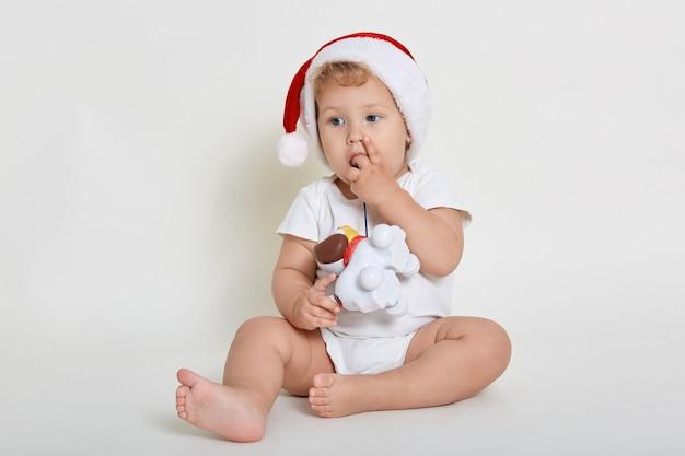 サンタクロースの帽子と白い壁をかぶって、プラスチックの犬のおもちゃで遊んで、目をそらし、指を噛み、床に裸足で座って、目をそらしている男の子。