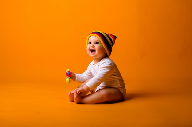 Baby boy in a white bodysuit and multicolored hat holding a toy, sitting on a orange wall