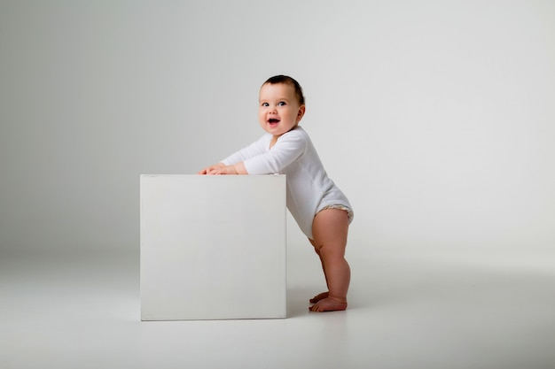 Baby boy in white bodysuit stands leaning on a white cube on a light wall