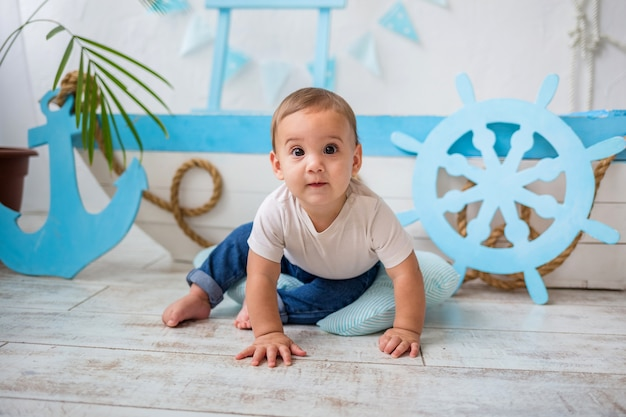 Baby boy in white t-shirt and jeans sitting on a wooden boat