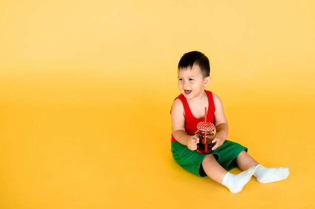 Baby boy with bottle or jug of juice or water in pop art style with yellow wall