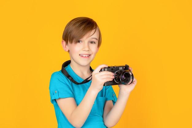 카메라와 함께 아기 소년입니다. 카메라를 들고 쾌활 한 웃는 아이. 빈티지 카메라를 사용하여 사진을 찍고 있는 어린 소년. 전문 카메라와 함께 스튜디오에서 아이입니다. 카메라를 사용하는 소년.