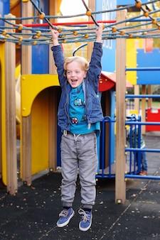 Мальчик с вьющимися волосами играет на детской площадке в парке развлечений