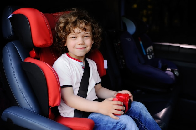 Baby boy with curly hair sitting in a child car seat with toy car in the hands