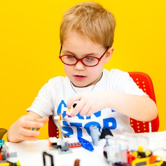 Baby boy with glasses playing with lego construction toy blocks at home