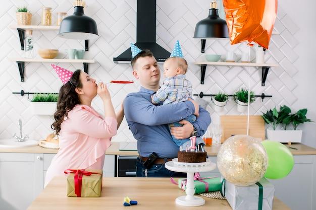 ケーキ、プレゼント、パーティーホーン、気球を自宅で1歳の誕生日を祝う明るい誕生日帽子の両親と男の子