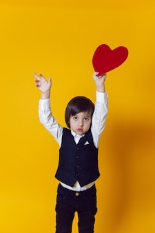 バレンタインの日に黄色の壁に立っている衣装を着た赤い紙のハートを持つ男の子