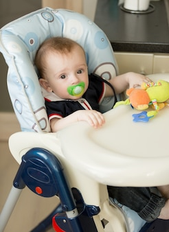 Baby boy with soother sitting in chair for feeding