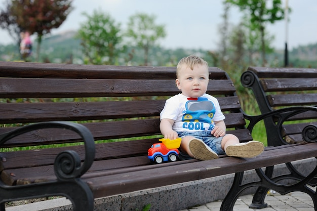 Baby boy with toy car in the hands and sitting on the bench