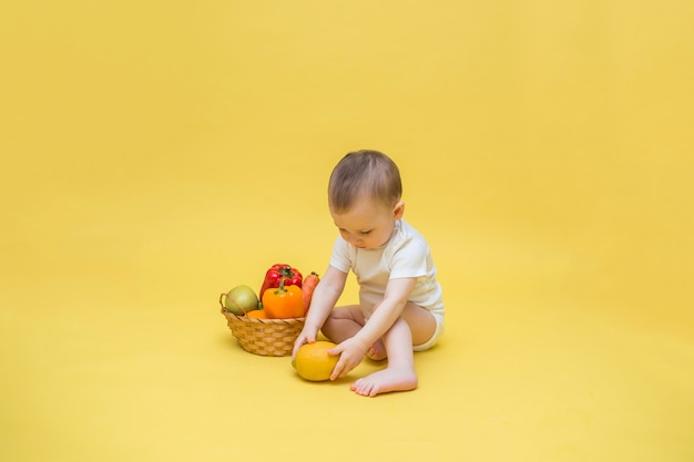 Baby boy with a wicker basket with vegetables and fruit on a yellow space. the boy is sitting in a white bodysuit and playing with a lemon.