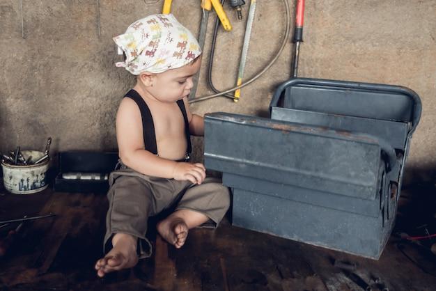 Механик baby boy - сидя за столом в магазине, с головой бандана