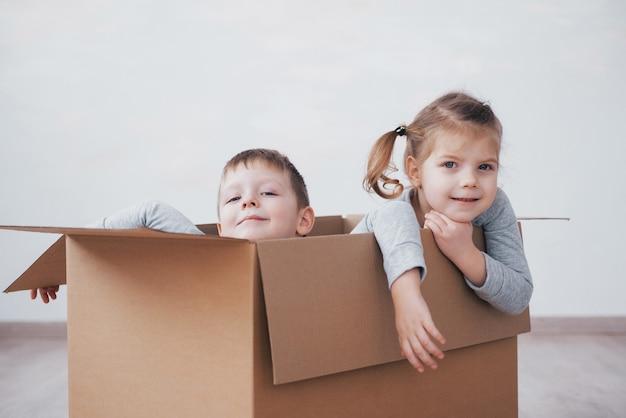Младенец брат и сестренка играют в картонных коробках в детской