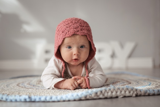 Baby in cap in real nursery, safety and care