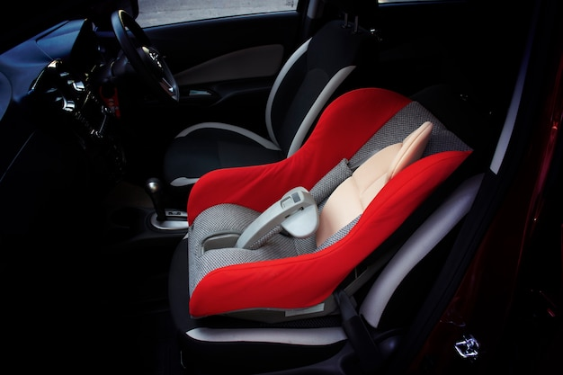 Baby car seat installed on a passenger seat in a car.