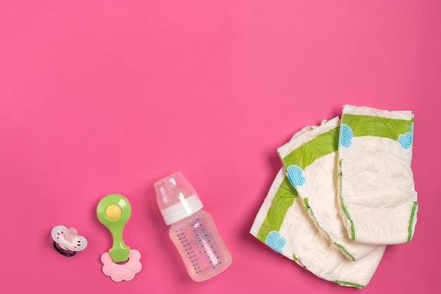 분홍색 배경에 베이비 케어 액세서리와 기저귀. 평면도. 공간을 복사합니다. 정물. 플랫 레이