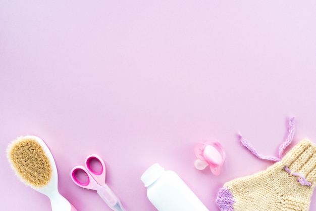 Baby care kit on pink background, top view, copyspace. flat composition with children's accessories, background.