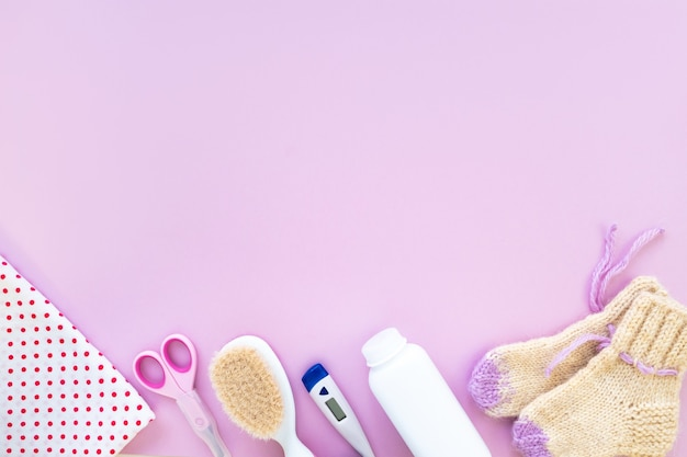 Baby care kit on pink background, top view, copyspace