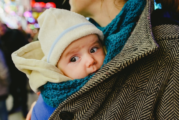 Baby carrying in a kangaroo scarf by his mother.