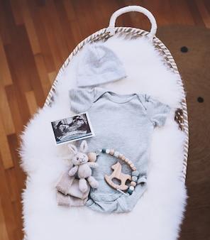 超音波画像と赤ちゃんの交換バスケット赤ちゃんのボディスーツソフトと木のおもちゃ新生児の背景