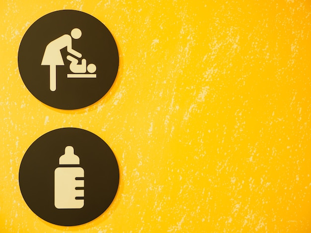 Baby changing room sign and symbol with yellow background.