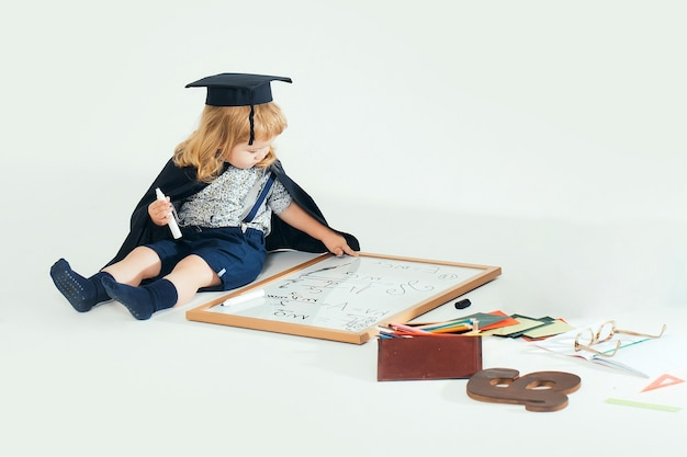 Baby child in academic gown and hat drawing by marker on blackboard near school supplies on white  isolated