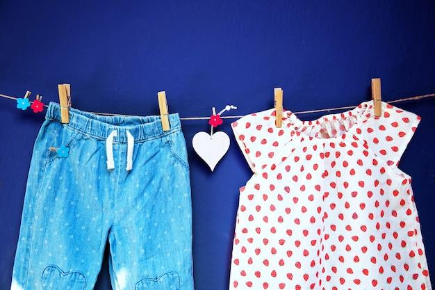 질감 있는 벽 배경의 빨랫줄에 있는 옷핀에 걸려 있는 아기 옷과 상품