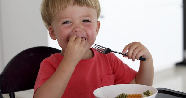 Baby child eating spaghetti at home in living room