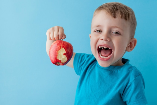 Baby child holding and eating red apple on blue, food, diet and healthy eating