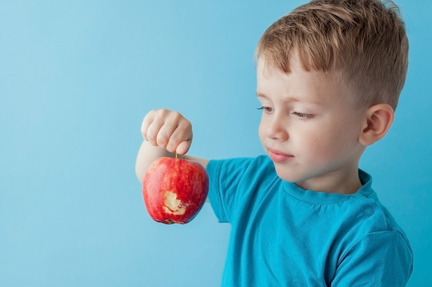 Baby child holding and eating red apple on blue wall, food, diet and healthy eating concept