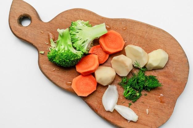 赤ちゃん子供子供食品、白い背景の上の木製のまな板に新鮮な健康野菜と夕食の昼食を準備するクローズアップ