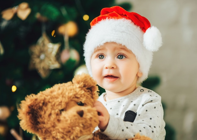 Baby in christmas hat with teddy bear in hands