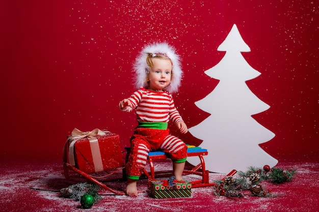 Baby in christmas pajamas and santa hat catches snow sitting on a sled with gift box and big white christmas tree on red background