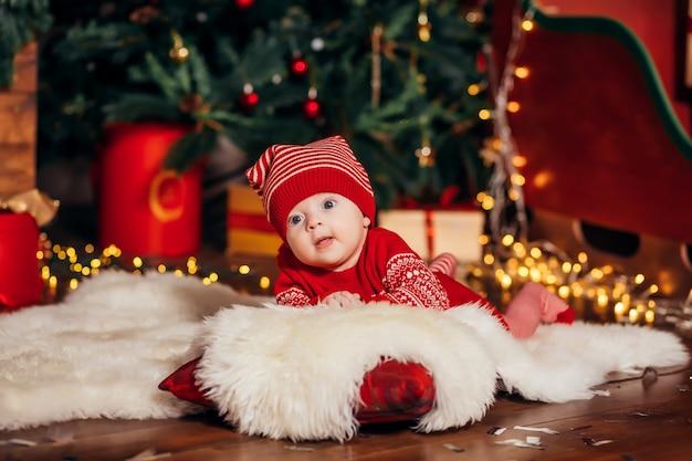 Baby next to the christmas tree