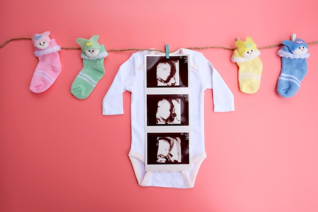Baby cloth with 4d ultrasound baby and socks on pink background.