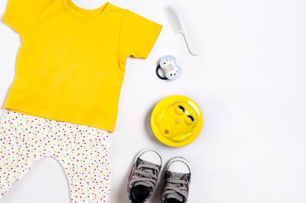 Детская одежда и аксессуары на белом фоне вид сверху