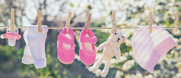 아기 옷과 액세서리는 야외에서 세탁 한 후에 밧줄에 무게를 weigh니다.