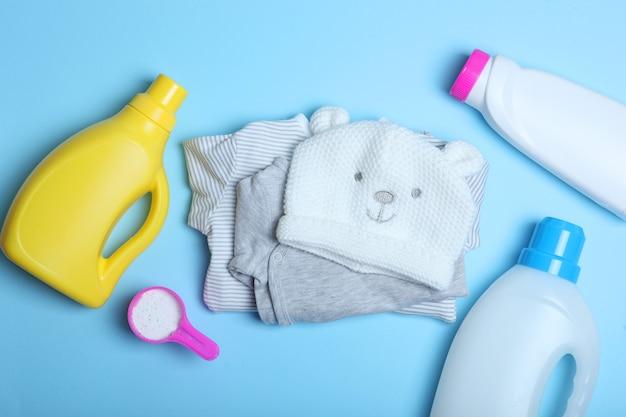 Детская одежда и моющие средства на цветном фоне вид сверху