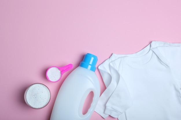 色付きの背景の上面図のベビー服と洗剤