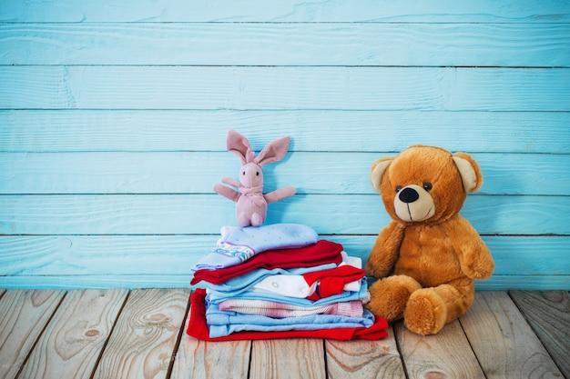 古い木製の背景にベビー服とおもちゃのクマ