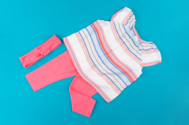 Baby clothes on blue  background top view