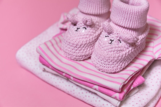 Baby clothes and crochet shoes for newborn girl on a pink background