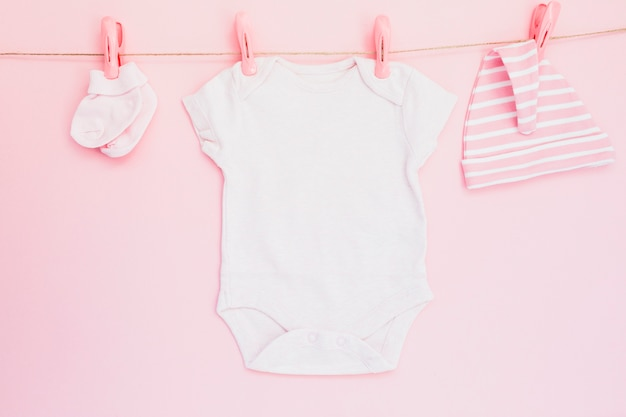 Baby clothes hanging on pink