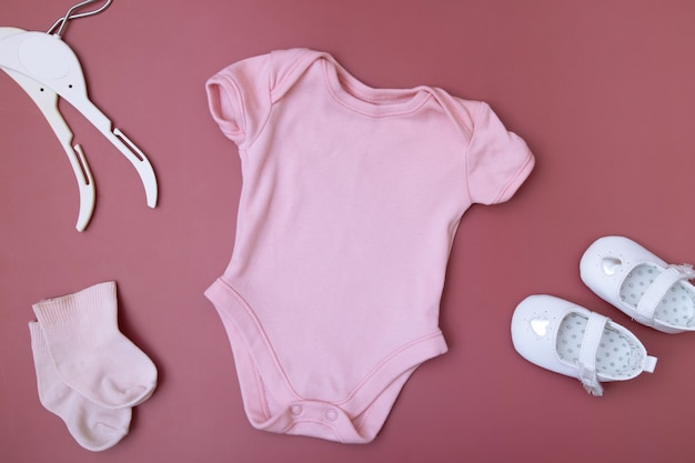 Детская одежда для текста на розовом фоне с аксессуарами