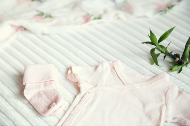 Baby clothes and necessities on light fabric background gentle soft and cozy mood
