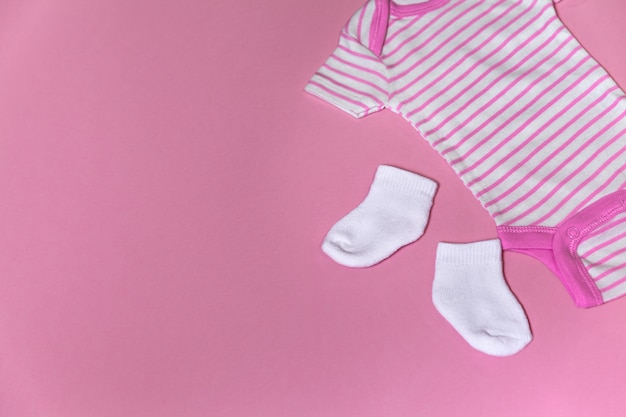 Baby clothes for newborn on a pink background with copy space on the left
