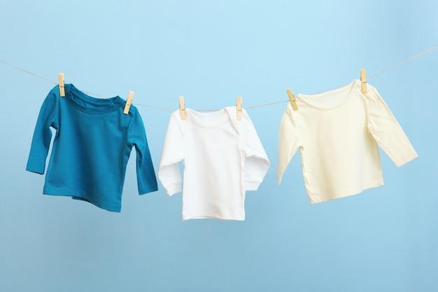 Детская одежда на веревке на цветном фоне